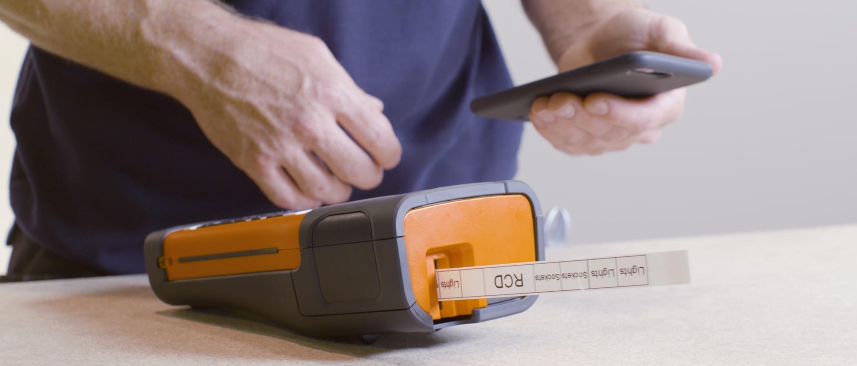 Hombre con móvil en una mano e impresora de etiquetas PT Brother