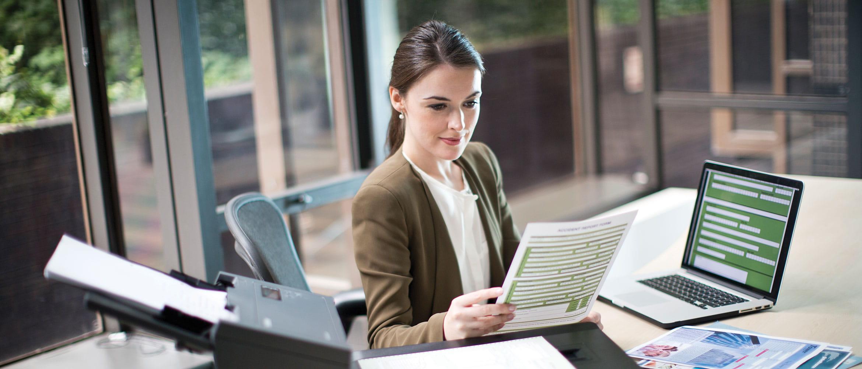 Mujer en oficina con portátil y escáner Brother
