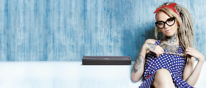 Hombre con barba tatuado sujetando impresora portátil PJ