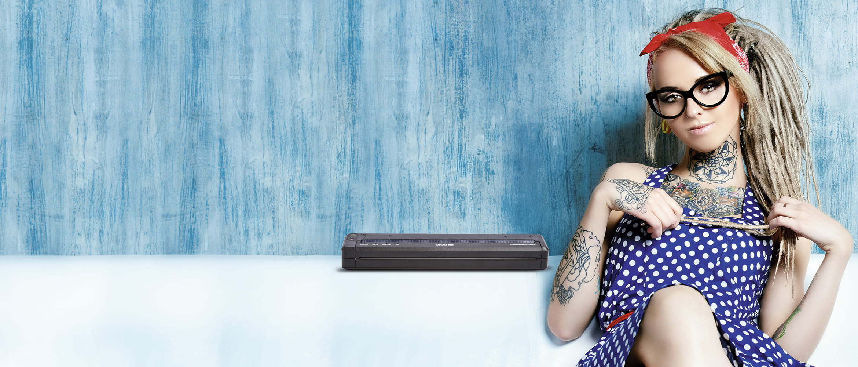 Chica con tatuajes en los brazos sentada junto a impresora portátil PJ Brother