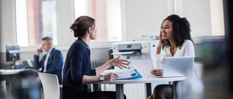 Dos mujeres charlando en una oficina junto a impresora Brother