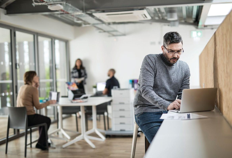 Personas en oficina con portátiles e impresora multifunción Brother al fondo