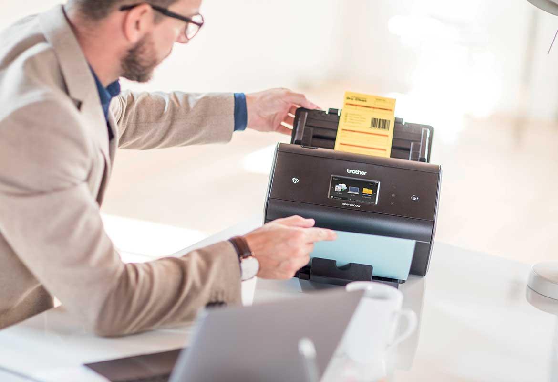 Hombre con gafas utilizando escáner Brother con aplicación Barcode para códigos de barras