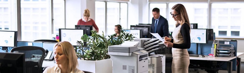 Mujer en oficina utilizando impresora láser monocromo serie L6000, Brother