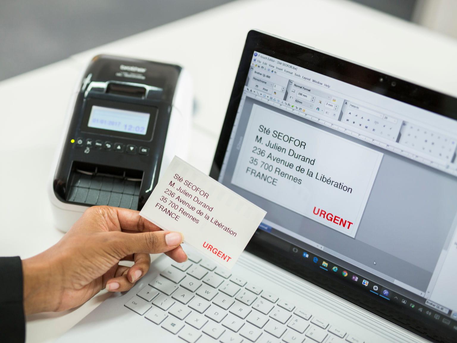Impresora de etiquetas QL-810W Brother junto a impresora portátil