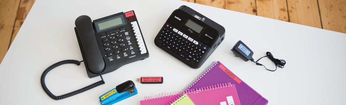 Teléfono junto a rotuladora PT-D450 Brother y material de oficina etiquetado
