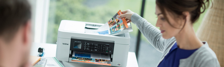 Mujer cogiendo hoja impresa a color de impresora Brother