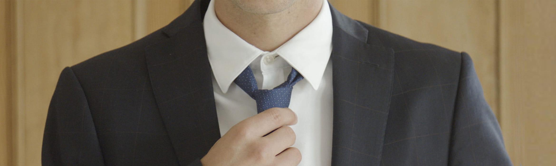 Detalle hombre anudando corbata