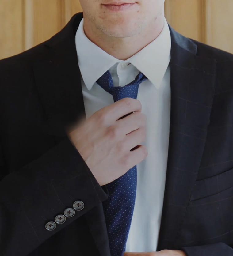 Hombre anudándose una corbata