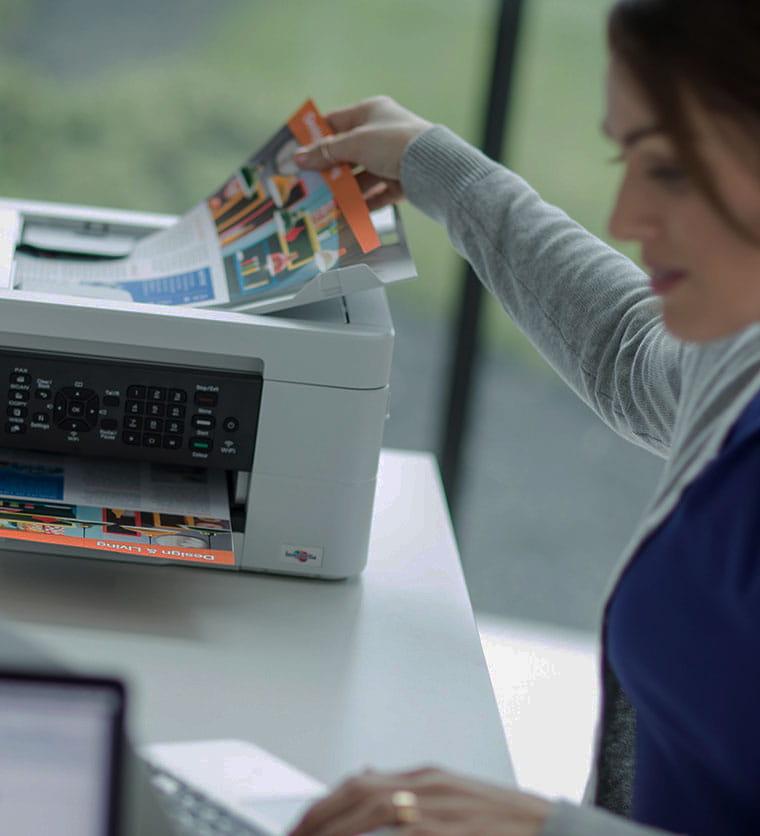 Mujer cogiendo hojas a color de impresora Brother