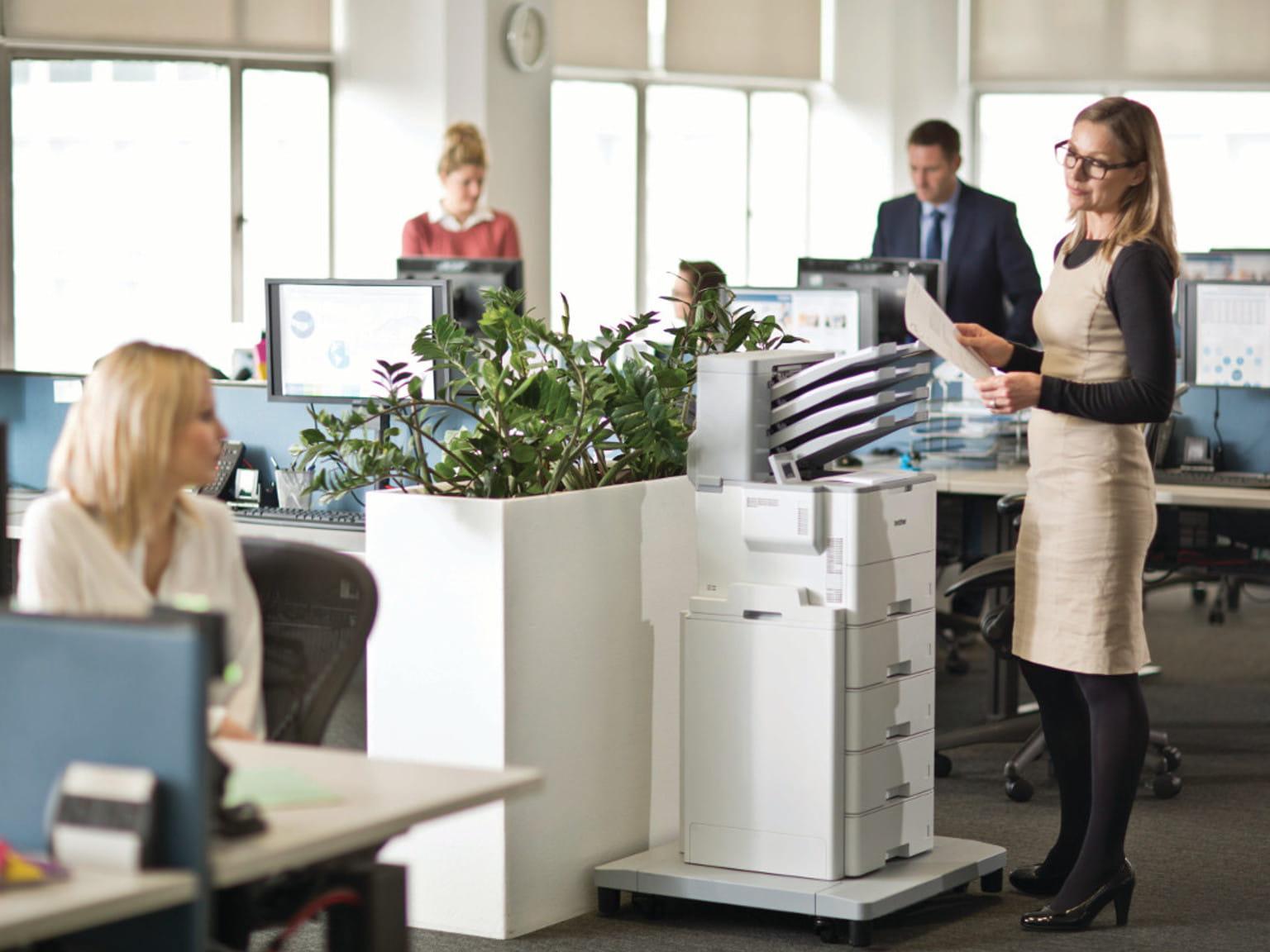Oficina con 5 personas y una impresora con base pedestal Brother