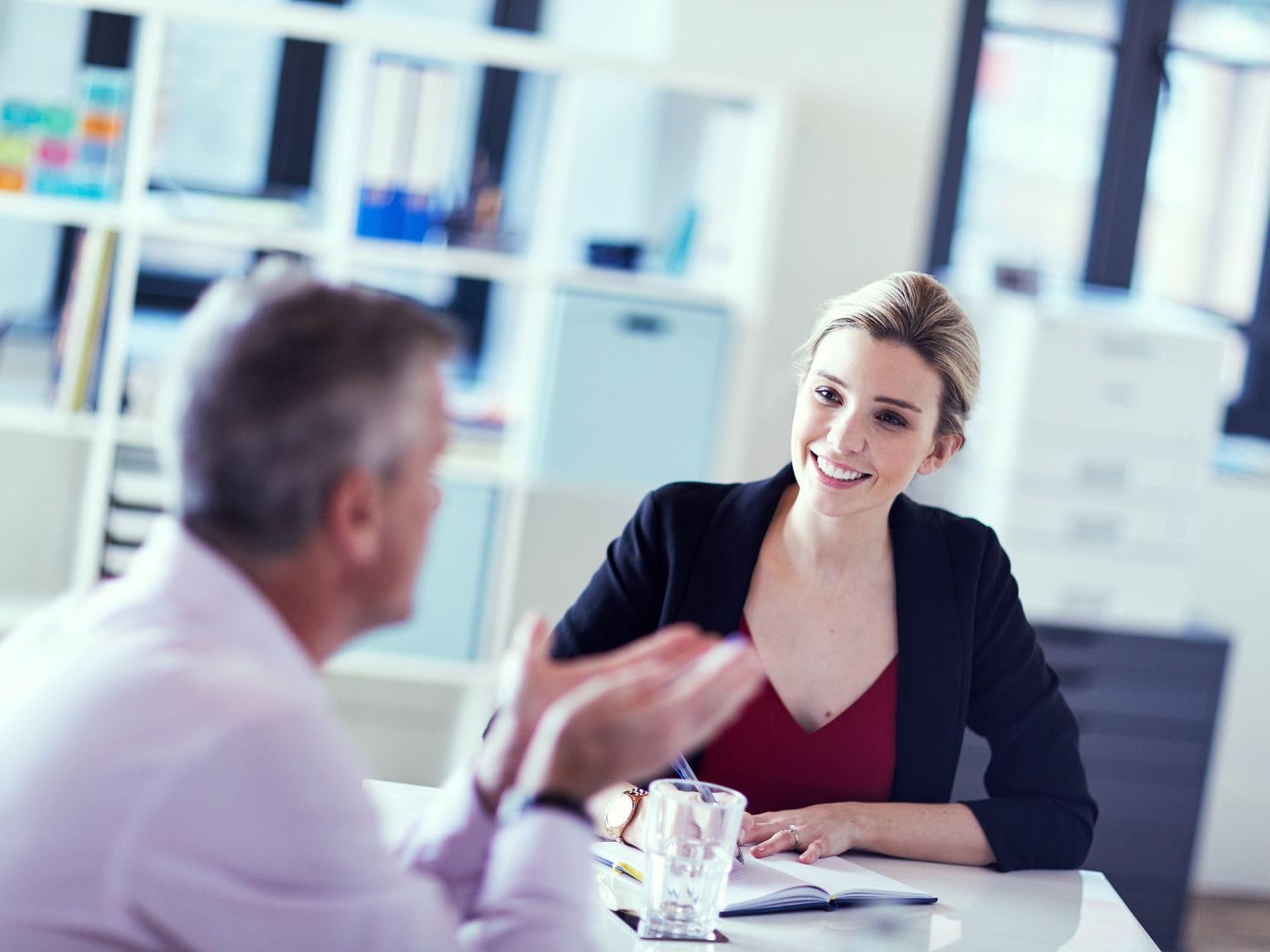 Mujer rubia charlando con un hombre en una oficina