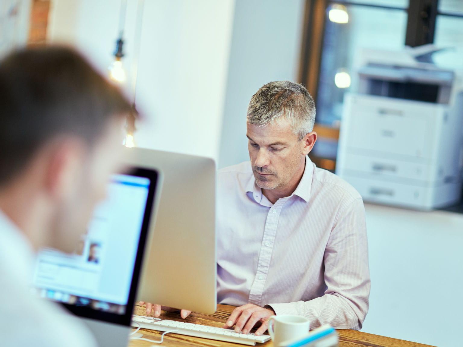 2 hombres trabajando con sus ordenadores
