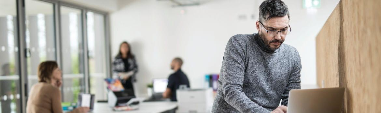 Hombre con jersey gris trabajando en ordenador portátil