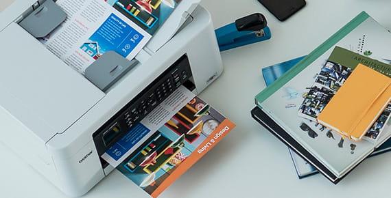 Impresora Brother junto a documentos a color