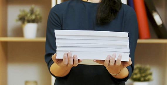 Mujer sosteniendo un taco de documentos