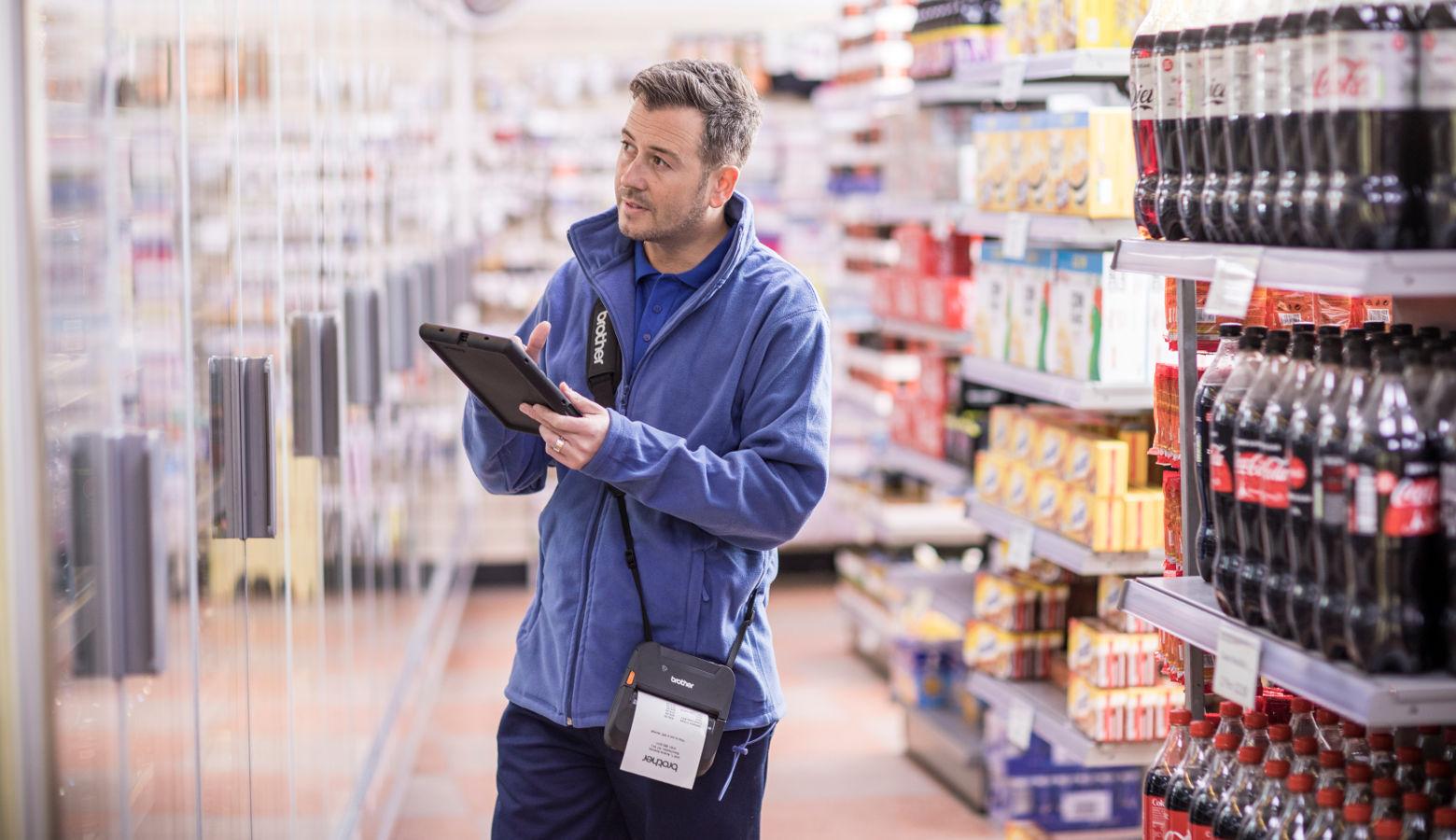 Operario con tablet e impresora de etiquetas RJ en supermercado