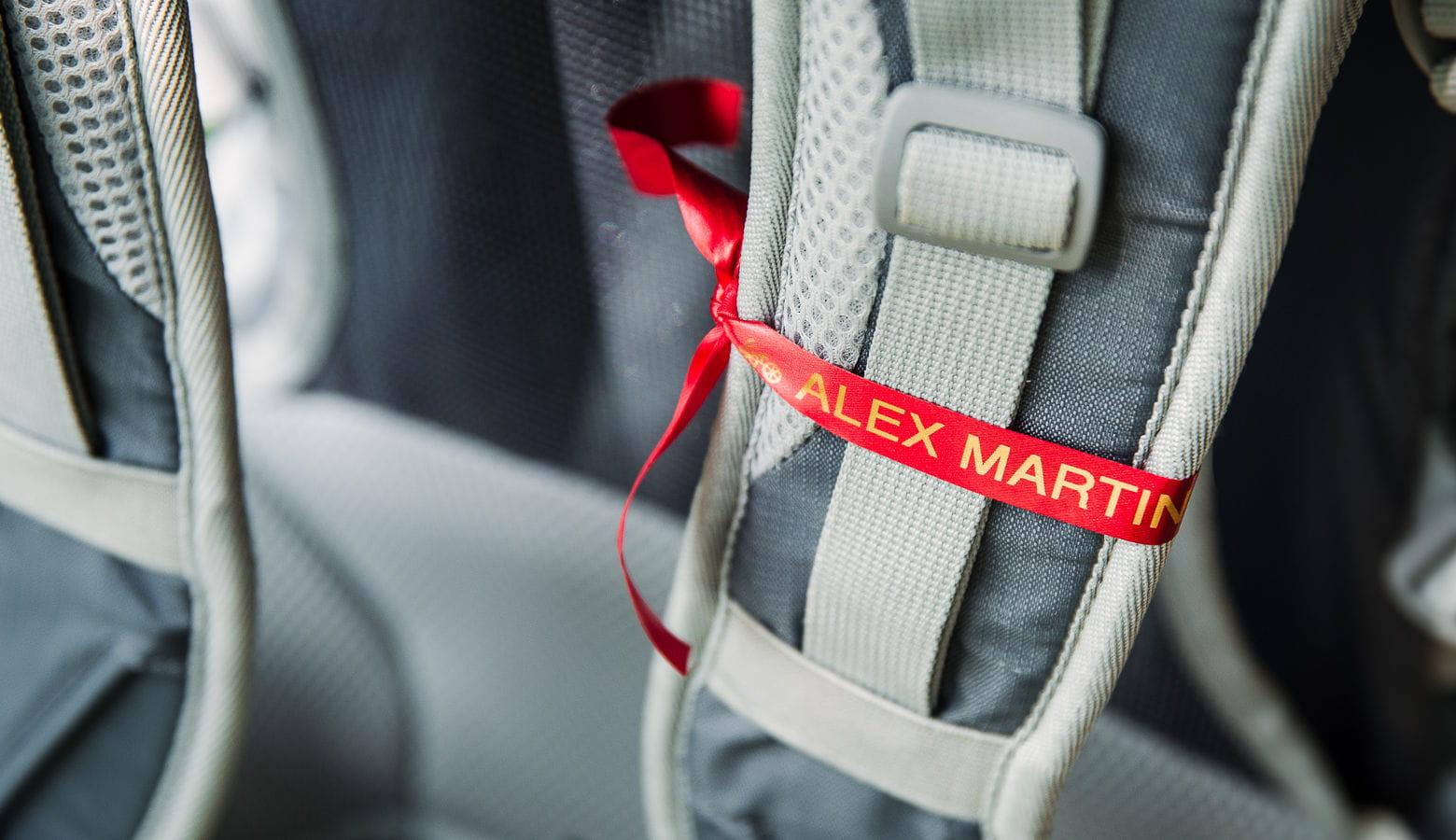Asa de mochila con etiqueta roja y letras doradas