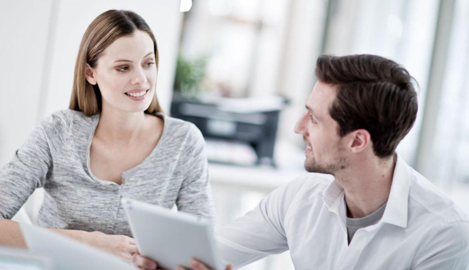 Mujer sonriente junto a hombre sosteniendo tablet