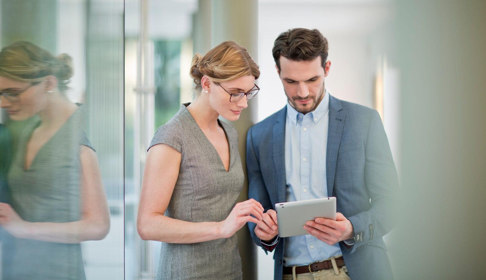 Mujer junto a hombre consultando tablet