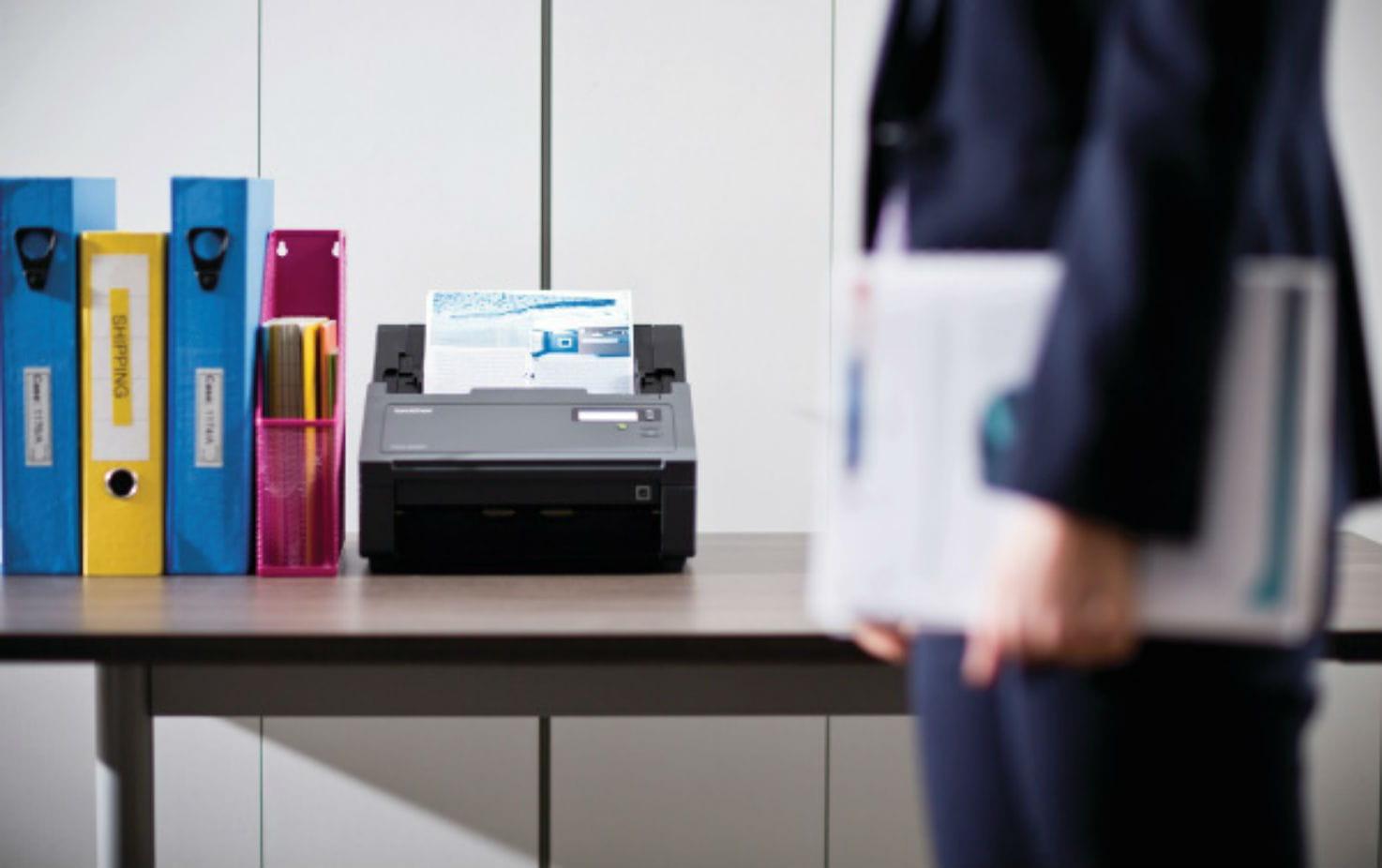 Escáner Brother junto a archivadores de colores