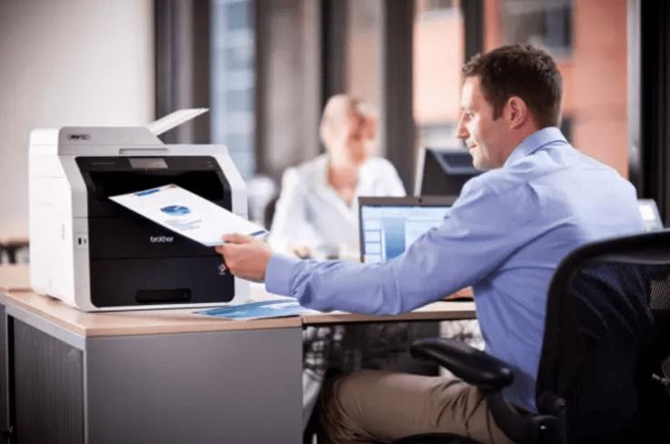 Hombre en oficina imprimiendo con impresora multifunción Brother