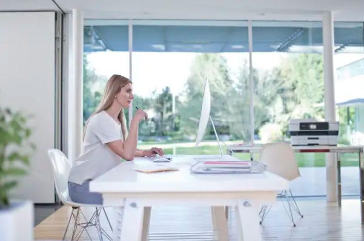 Mujer en oficina mirando monitor de ordenador
