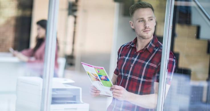 Chico con camisa de cuadros sujetando folio a color mirando a través de ventana