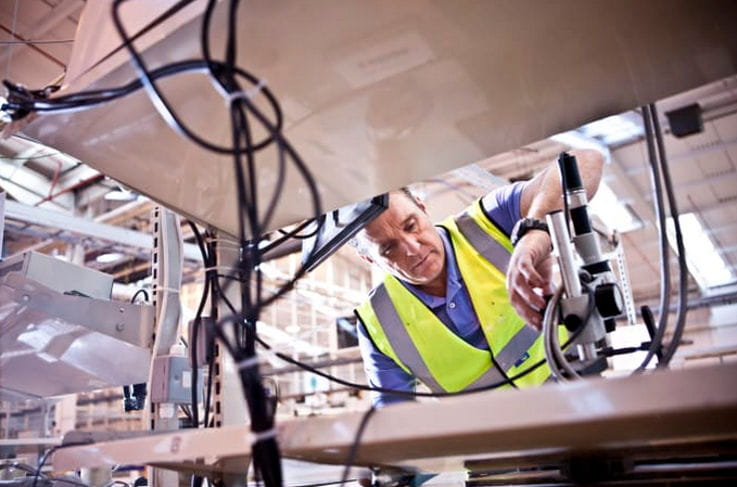 Hombre con chaleco amarillo trabajando en máquina