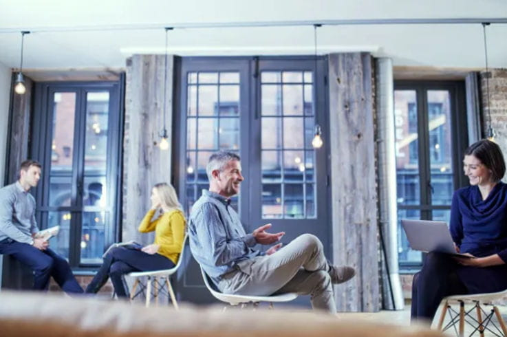 2 hombres y 2 mujeres sentados en sillas en una oficina