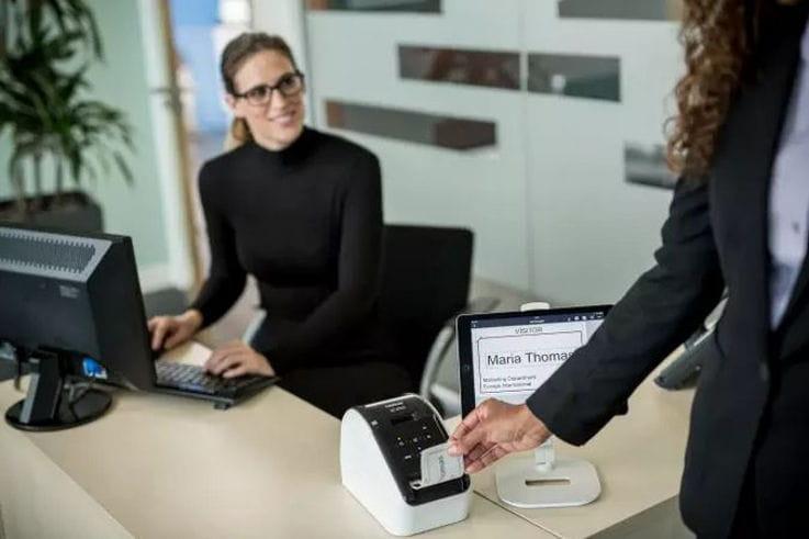 Mujeres en oficina utilizando impresora de etiquetas Brother