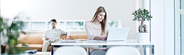 mujer sentada en un escritorio en una computadora portátil