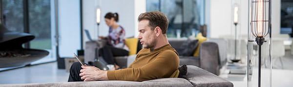hombre sentado en un sofá trabajando en una tableta